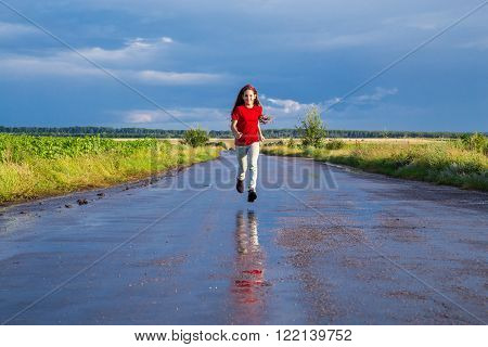 Happy girl running on wet road after rain