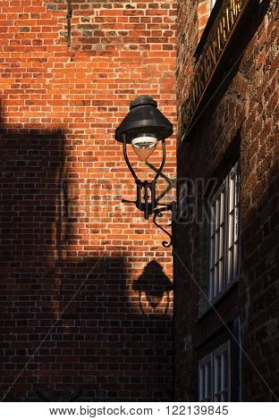 Street lamp with shade between historic red brick walls in a narrow street in the Hanseatic old town of Luebeck, Europe, North Germany