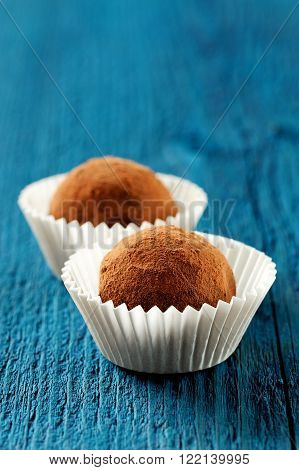 Two round homemade cocoa truffles in crimped paper plates on deep blue backgrpund