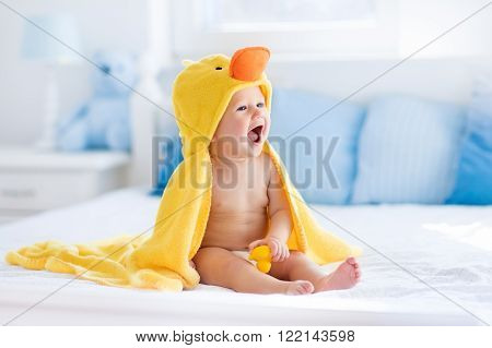 Happy laughing baby wearing yellow hooded duck towel sitting on parents bed after bath or shower. Clean dry child in bedroom. Bathing and washing of little kids. Children hygiene. Textile for infants.
