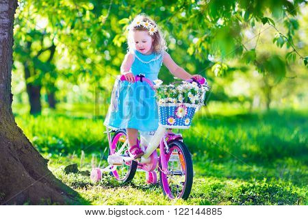 Happy child riding a bike. Cute kid biking outdoors. Little girl in a blue dress on a pink bicycle with daisy flowers in a basket. Healthy preschool children summer activity. Kids playing outside.