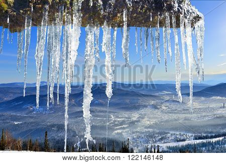 Ice melting icicles on a background of snow-capped mountains and blue sky - signs of the coming spring