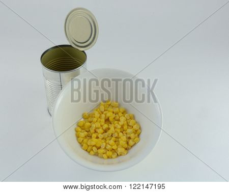 Canned corn in bowl and can on white background