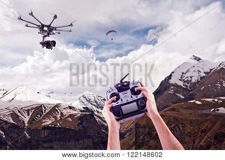 In the hands of a professional radio control mules on the background of beautiful mountains. Remote radio control copter in the young man's hands. Management of professional drone