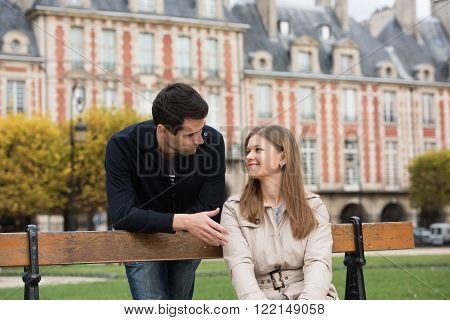 young couple having romantic conversation on the bench in park in Paris, France