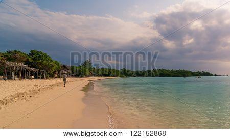 In the picture a man walking alone on a beautiful beach in Zanzibar in the evening. Republic of Tanzania.