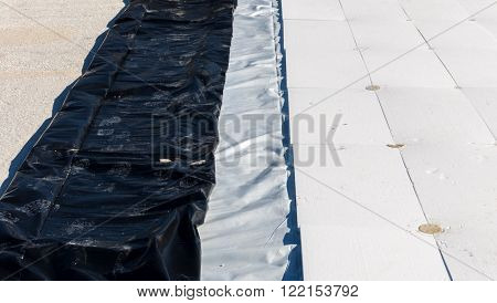 insulating material panels in white pvc with fixed dowels on the roof of a floor to the terrace