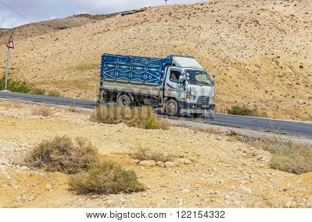 Madaba, Jordan - October 27, 2015: Truck painted ornament descends down the road in a mountainous desert of Jordan. The passenger in the cab of the truck looks ahead with a bored face.