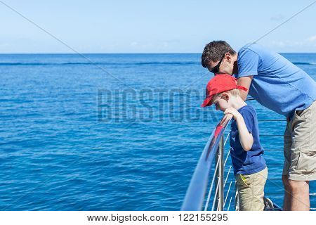 family of two at the boat looking at water