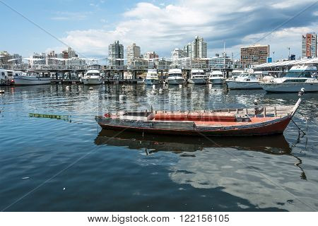 MALDONADO FEBRUARY 29 2016 - Classic Red Fishing Boat moored in front of the yachts of the rich people in Punta del Este harbor Uruguay