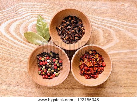 Three wooden bowls with pepper cloves and slices of dried peppers on a light wooden table. Next to the bowl are two of dried bay leaves.