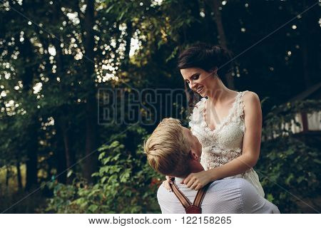 groom holds his bride in his arms somewhere in the nature