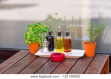 Balsamic vinegar and oil bottles and condiments on the table in an outdoor cafe