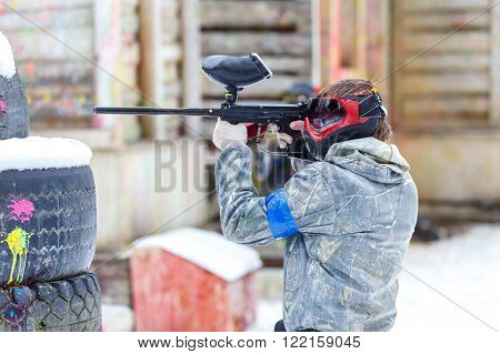 Paintball Game In Winter. Man Shooting From Marker.