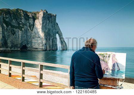 Etretat, France - September 23rd, 2014: Painter paints the white cliffs of Etretat with the famous Natural Arch La Porte d`Aval, Alabaster Coast, Normandy,