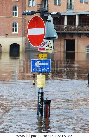 Traffic signs on bank of flooded River Ouse, York.