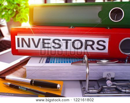 Red Office Folder with Inscription Investors on Office Desktop with Office Supplies and Modern Laptop. Investors Business Concept on Blurred Background. Investors - Toned Image. 3D.