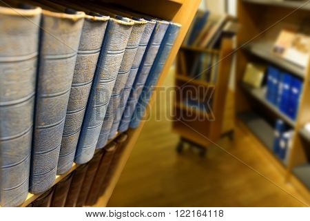 Vintage books with blue backs in shelf in library