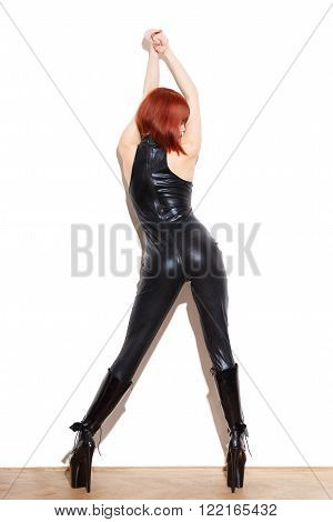 Sexy redhead woman in latex catsuit and high heel boots posing at wall bdsm