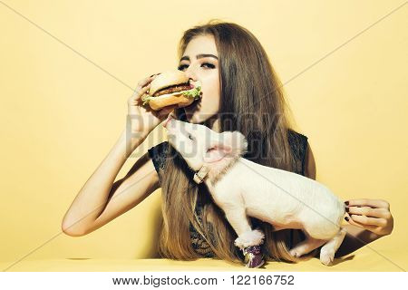 Beautiful young sensual woman and cute pink small pig pet in cloth eating tasty big fresh burger on yellow background horizontal picture