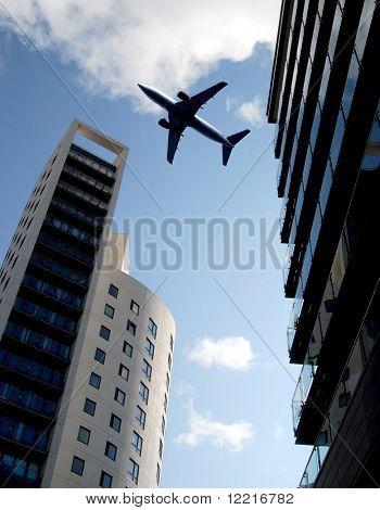 Jet passenger aircraft flies over tower blocks