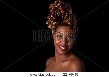 Young Beautiful African Woman Wearing A Traditional Headscarf, Isolated Over Black Background