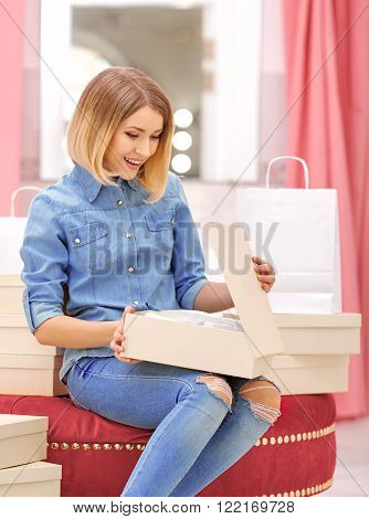 Want to buy them. Delighted positive woman holding box with shoes and sitting on the pouf while shopping