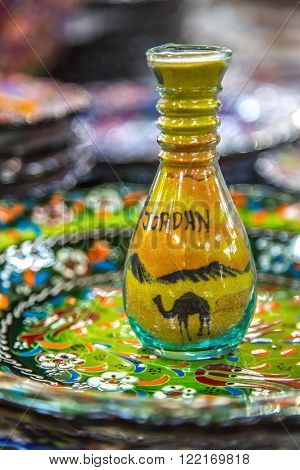 Bottle with sand picture is painted on the color pattern plate. Jordan souvenir. Madaba, Jordan.