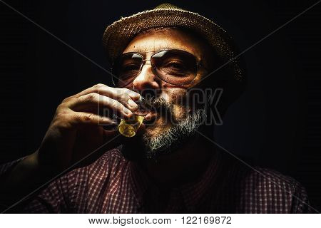 Happy middle age man drinking an alcoholic drink.