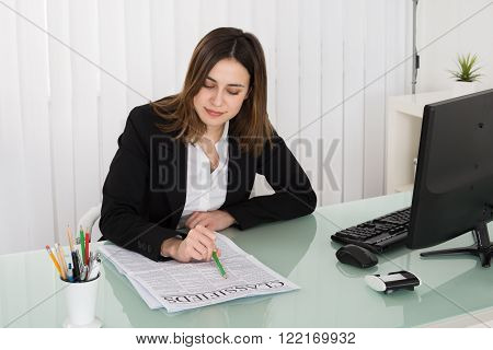 Young Businesswoman Reading Classifieds On Newspaper In Office