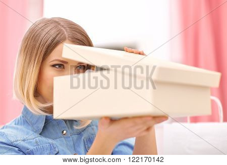 What is here. Cheerful beautiful positive woman holding box with shoes and opening it while shopping