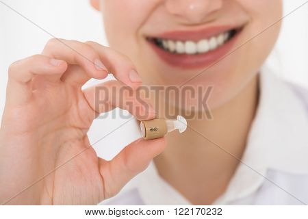 Close-up Of Young Happy Female Doctor Holding Hearing Aid