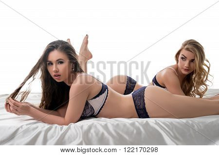 Charming girls advertise erotic lingerie in studio, isolated on white background