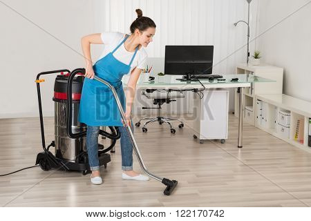 Female Janitor Cleaning Floor With Vacuum Cleaner In Office