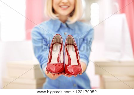 My favorites. Close up of red shoes in hands of pleasant attractive woman holding them and smiling while sitting in the pouf in a shop ** Note: Soft Focus at 100%, best at smaller sizes