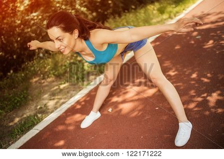 Happy young beautiful woman doing exercise at tartan track on a sunny day.