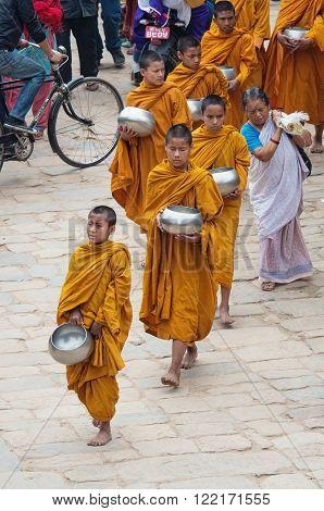 BHAKTAPUR NEPAL - APRIL 5: Little Buddhist monks on the street on April 05 2014 in Bhaktapur Nepal