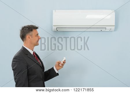 Businessman Holding Remote Control Air Conditioner In Office
