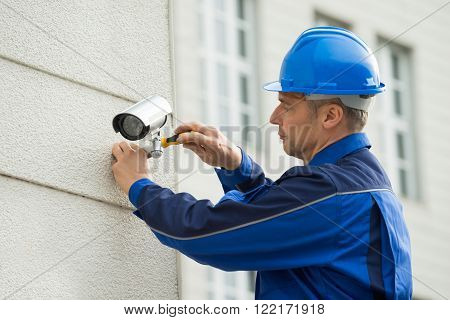 Mature Technician Installing Camera On Wall With Screwdriver
