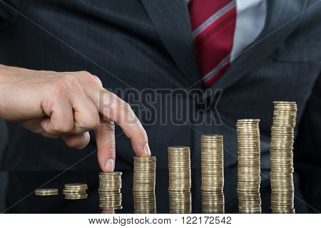 Close-up Of Businessman Fingers Walking On Pile Of Coins