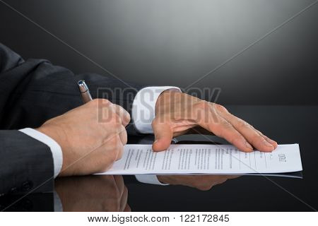 Close-up Of Businessperson Signing Contract Paper With Pen