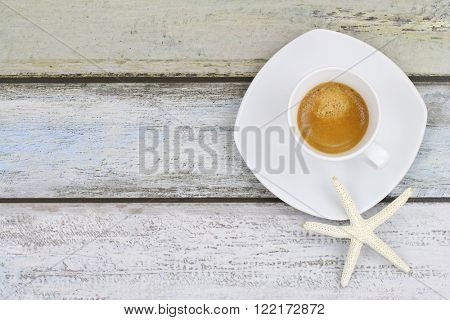 Star fish on freshly brewed espresso coffee on blue green wooden looking tile