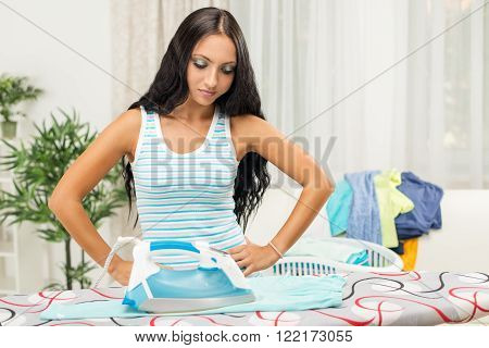 Boredom young housewife ironing clothes in home