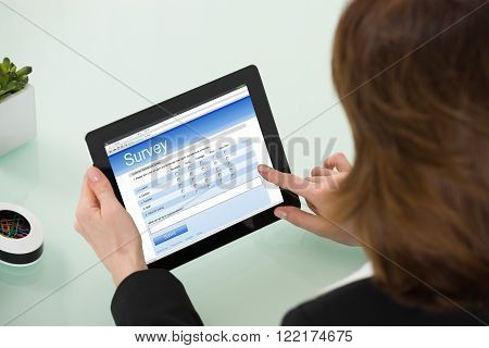 Close-up Of Businesswoman Filling Online Survey Form On Digital Tablet