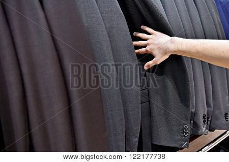 Detail shot with hand picking out man suit jacket in a suit shop