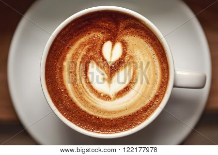 White cup of cappuccino with beautiful foam on wooden table. Latte art, macro, top view.