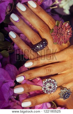 bright colorfull shot of african tanned hands with manicure among pink flowers wearing jewellery among flowers close up