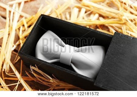 White leather bow tie in a special packaging on a thatch, close up