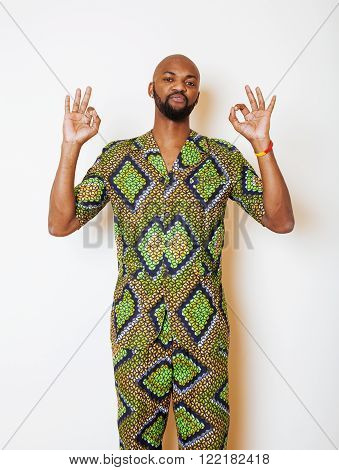 portrait of young handsome african man wearing bright green national costume smiling gesturing, entertainment stuff