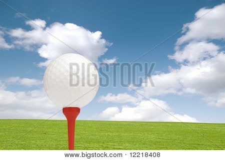Golf ball on tee with grass and cloudy blue sky